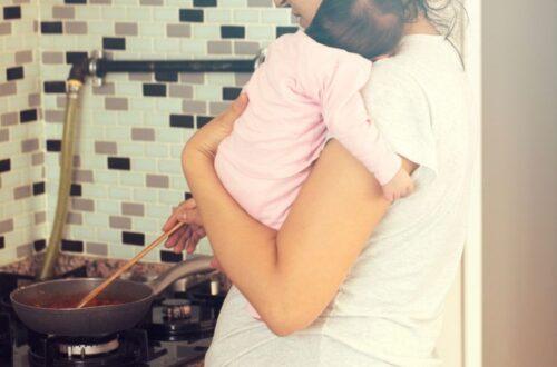 בדידות אחרי לידה אישה מבשלת אוכל עם תינוק