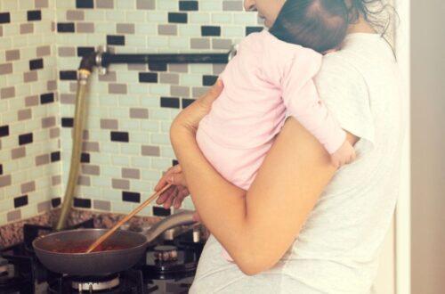 בדידות אחרי לידה אמא מבשלת בסיר על הגז ותינוק על הידיים שלה
