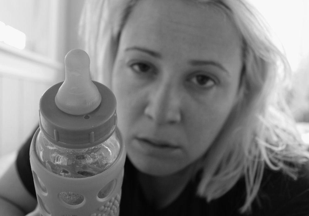 אמא אחרי לידה עם בקבוק ביד עייפה תשושה