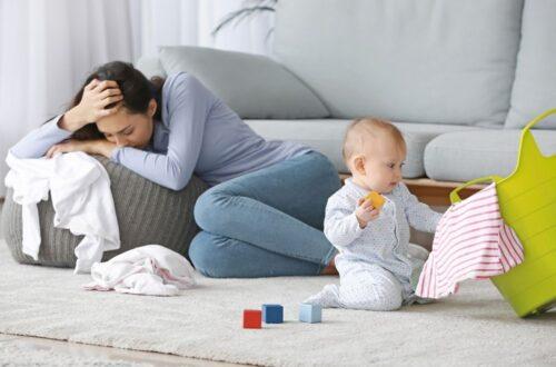 אישה עצובה אחרי לידה שזקוקה לעזרה תינוק משחק לידה עם סל צהוב