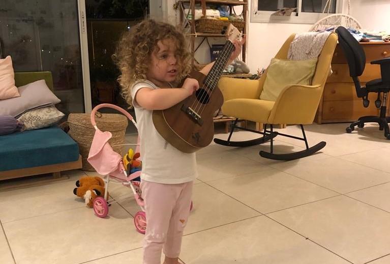 ילדה מנגנת על גיטרה